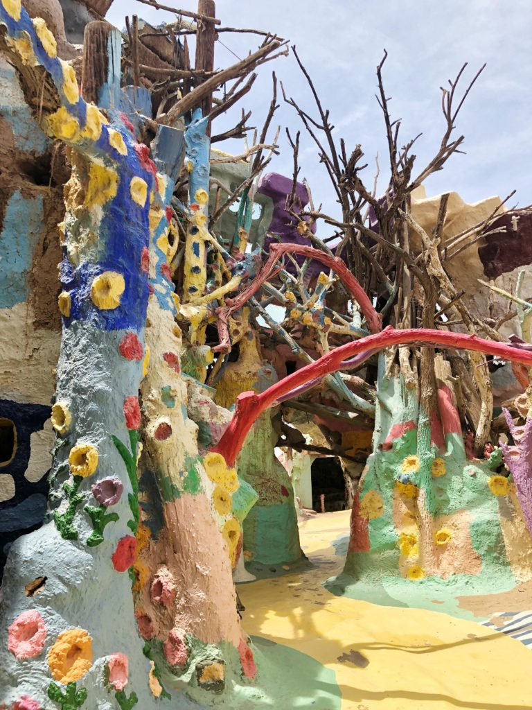 The structure to the side of Salvation Mountain appears to be made from hay and tree branches